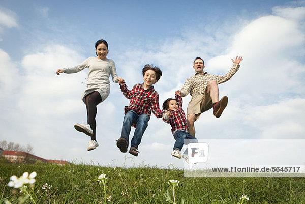 Eine Familie  die Händchen hält und in die Luft springt.