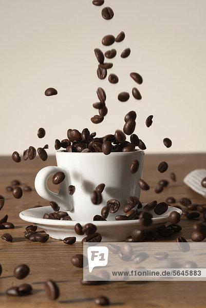 Kaffeebohnen  die in eine Tasse gegossen werden