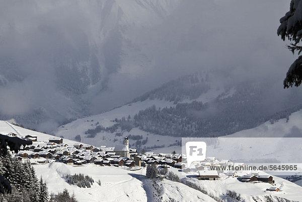 Verschneites Dorf mit Bergkette und Tal im Hintergrund