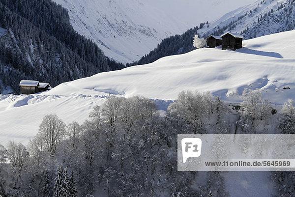 Winterlandschaft des Berges mit Blockhütten