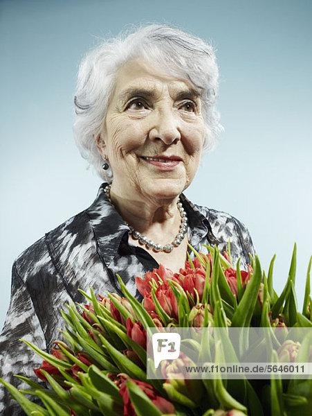 Eine ältere Frau  die einen Strauß Tulpen erhält.