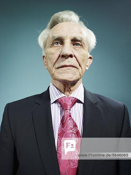 Ein eleganter Senior in Anzug und rosa Krawatte.