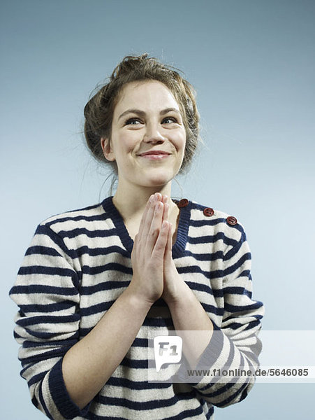Eine junge Frau mit ihren Händen zusammen mit einem Blick voller Hoffnung.