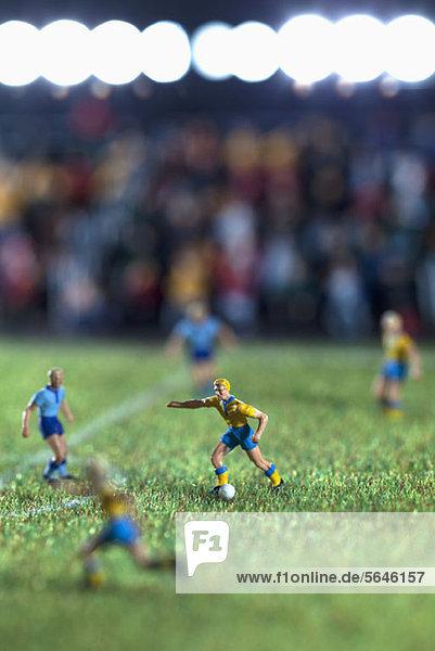 Miniaturfiguren zweier Fußballmannschaften bei einem Fußballspiel