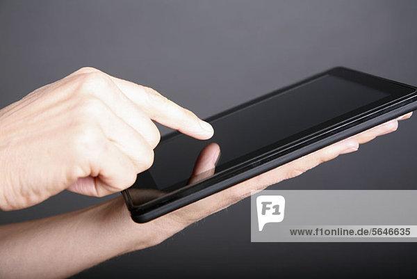 Ein Mann  der ein digitales Tablett benutzt  Nahaufnahme der Hand.