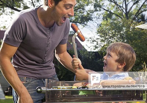 Vater und Sohn beim Grillen