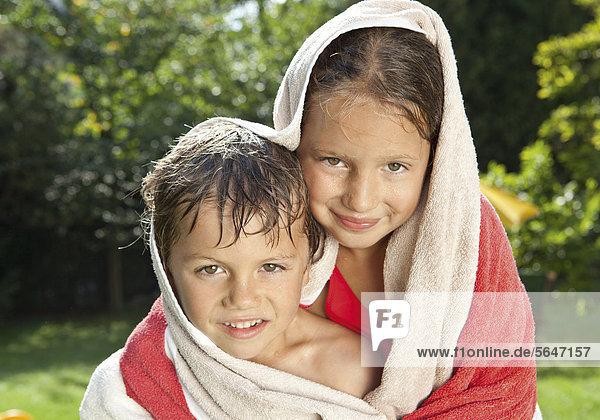 Zwei Kinder in Badehandtuch gehüllt