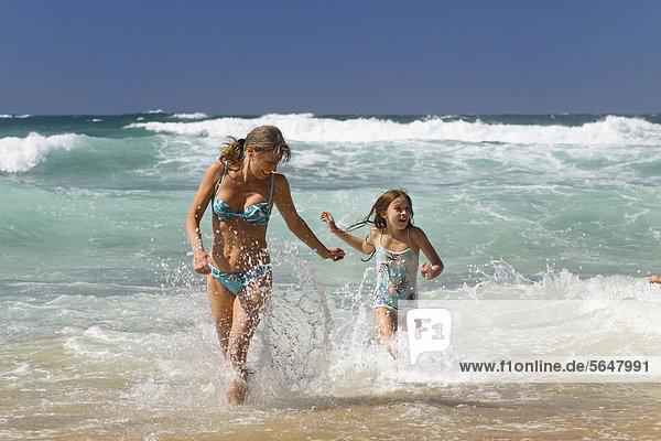 Mother and daughter bathing at the beach of Praia da Castelejo  Atlantic coast  Algarve  Portugal  Europe