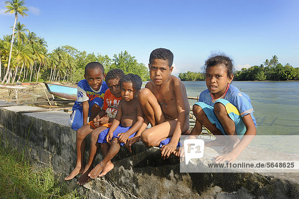Papuan children in front of a lagoon  Biak Island  off the island of Papua New Guinea  Indonesia  Southeast Asia  Asia