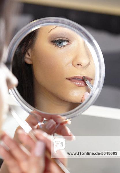 Junge Frau mit Handspiegel und Lippenstift-Pinsel