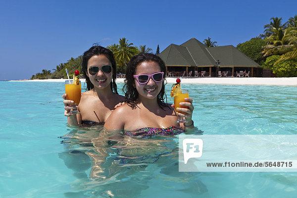 Zwei Mädchen  ca. 14 und 18 Jahre  mit Sonnenbrillen  trinken Cocktails in einer türkisfarbenen Lagune im Meer  hinten Malediveninsel Paradise Island  Lakanfinolhu  Malediven  Indischer Ozean  Asien