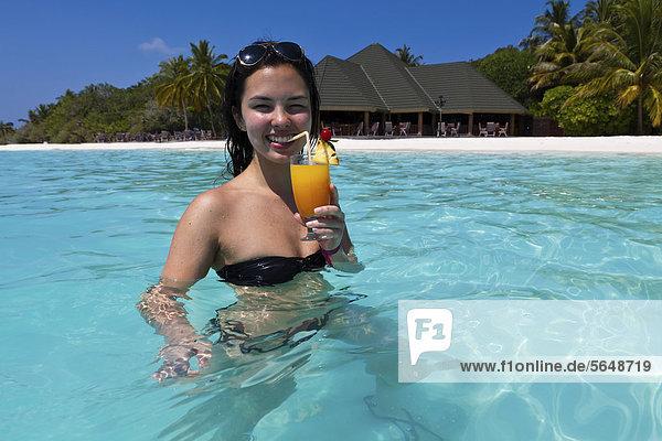 Junge Frau trinkt einen Cocktail in einer türkisfarbenen Lagune im Meer  hinten Malediveninsel Paradise Island  Lakanfinolhu  Malediven  Indischer Ozean  Asien