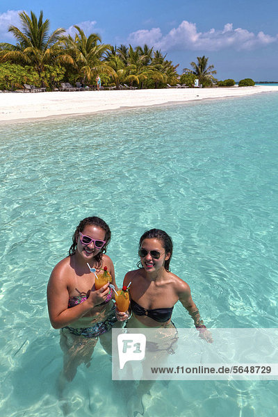 Zwei Mädchen  ca. 14 und 18 Jahre  mit Sonnenbrillen  trinken Cocktails in einer türkisfarbenen Lagune im Meer  hinten Malediveninsel  Malediven  Indischer Ozean  Asien