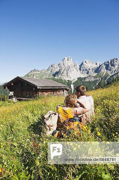 Österreich  Salzburg  Filzmoos  Paar sitzend und ruhend auf der Alm