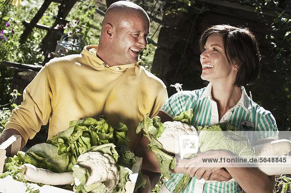 Österreich  Salzburg  Flachau  Paar mit Gemüse im Garten  lächelnd