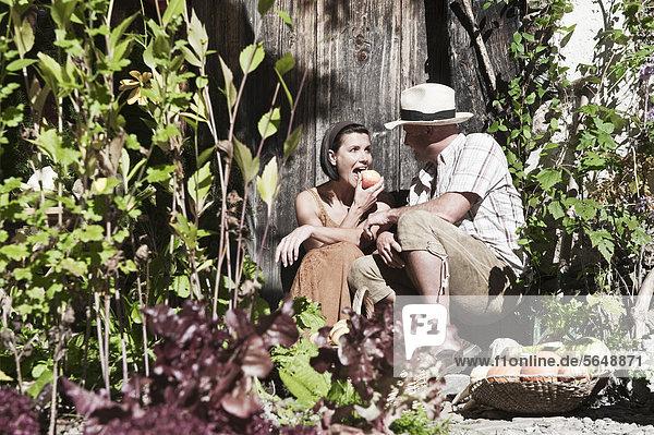 Österreich  Salzburg  Flachau  Paar im Garten sitzend