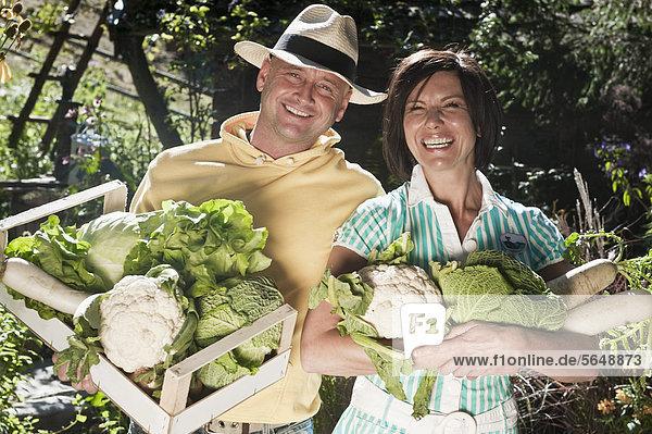 Österreich  Salzburg  Flachau  Paar mit Gemüse im Garten  lächelnd  Portrait