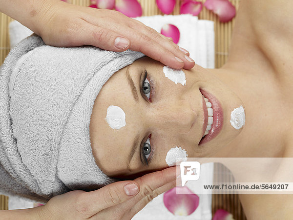 Masseurin mit Gesichtsmassage für junge Frauen im Spa