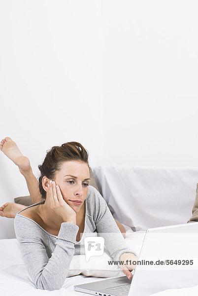 Deutschland  Nordrhein-Westfalen  Düsseldorf  Junge Frau auf dem Bett liegend mit Laptop