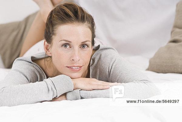 Deutschland  Nordrhein-Westfalen  Düsseldorf  Junge Frau auf dem Bett liegend  lächelnd  Portrait
