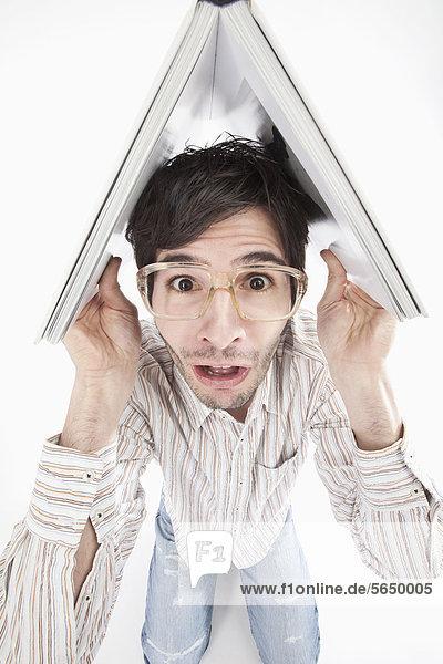 Junger Mann mit verrückter Brille und Buch  Portrait