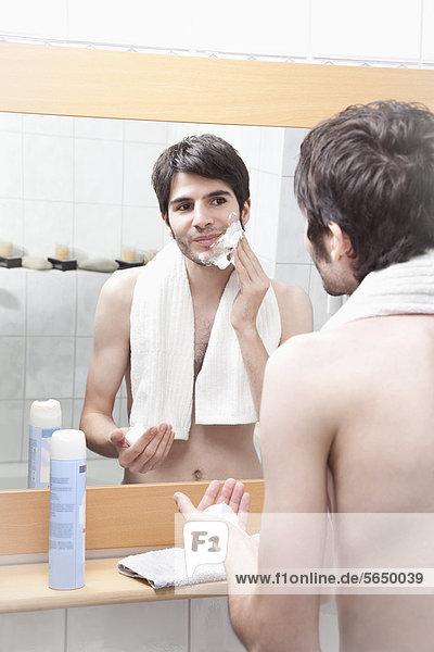 Junger Mann beim Auftragen von Rasiercreme im Bad