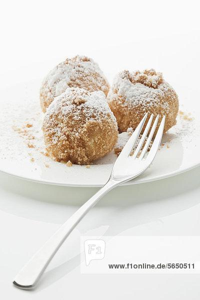 Aprikosenknödel im Teller auf weißem Grund