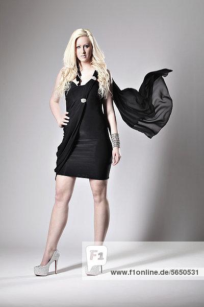 Blonde Frau in schwarzem Kleid