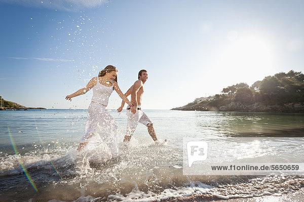 Spanien  Mallorca  Paar läuft am Strand entlang