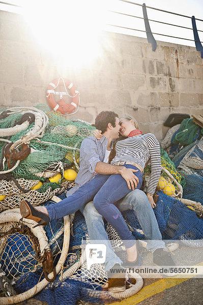Spanien  Mallorca  Paar am Hafen mit Fischernetzen  lächelnd