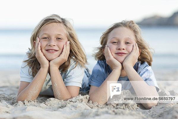 Spain  Mallorca  Children lying in sand on beach  smiling  portrait