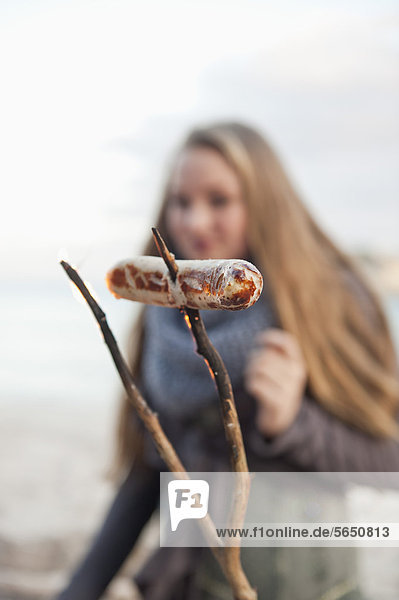 Spain  Mallorca  Grilled sausage with teenage girl in background