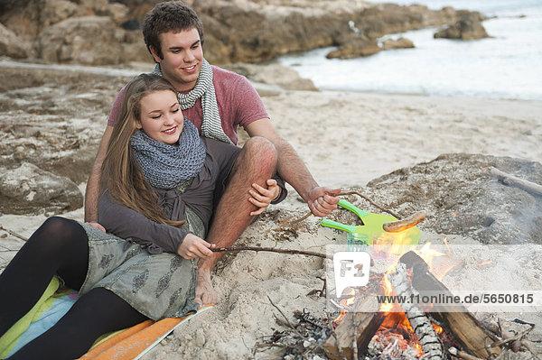 Spain  Mallorca  Couple preparing sausages on beach  smiling