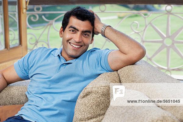Porträt eines Mannes  der auf einem Sofa sitzt