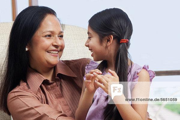 Mädchen sitzend bei ihrer Großmutter