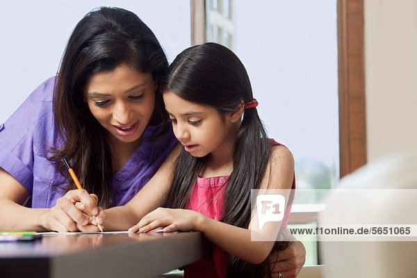 Mutter  die ihrer Tochter das Schreiben beibringt.