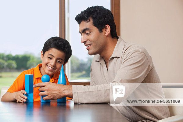 Vater und Sohn spielen mit Bausteinen