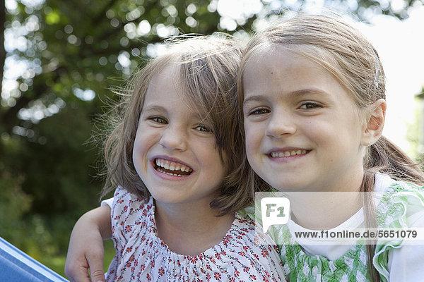 Girls in garden  smiling  portrait