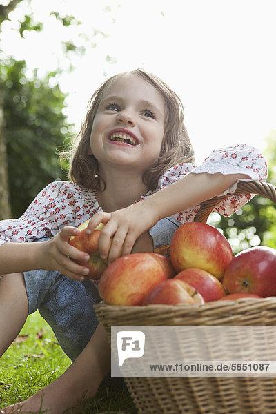 Mädchen sitzend mit Apfelkorb