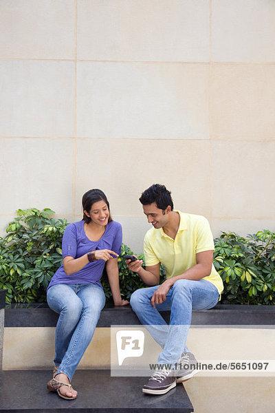 Ein Paar schaut sich eine SMS an.