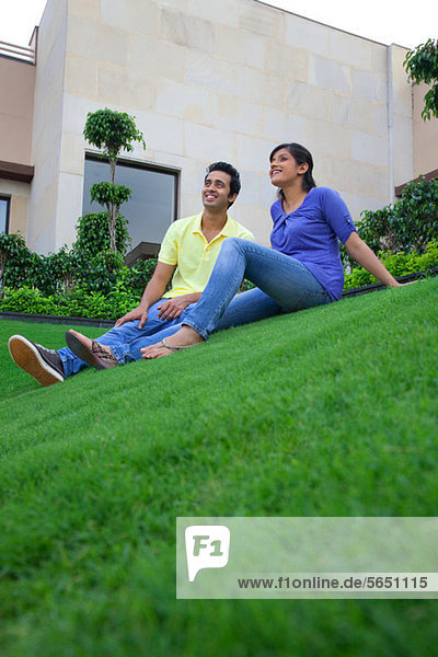 Paar auf dem Rasen sitzend