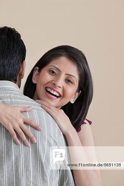 Porträt einer Frau  die ihren Mann umarmt.
