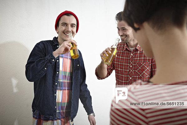 Männer und Frauen  die Bier trinken  lächelnd