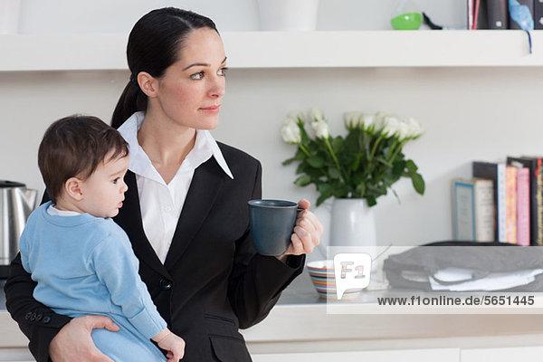 Geschäftsfrau mit Baby-Sohn und Kaffeetasse
