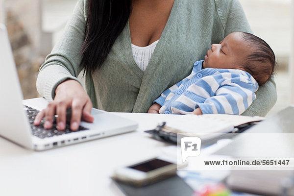 Mutter hält Baby und benutzt Laptop