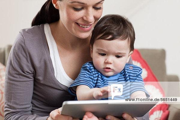 Mutter und Baby beim Betrachten des digitalen Tabletts