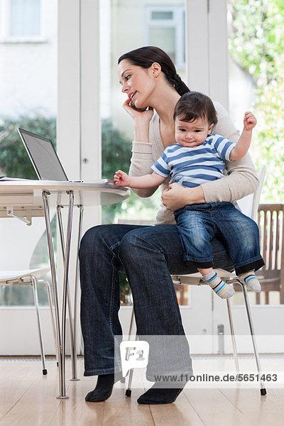 Mutter hält Baby Junge  mit Handy und Laptop