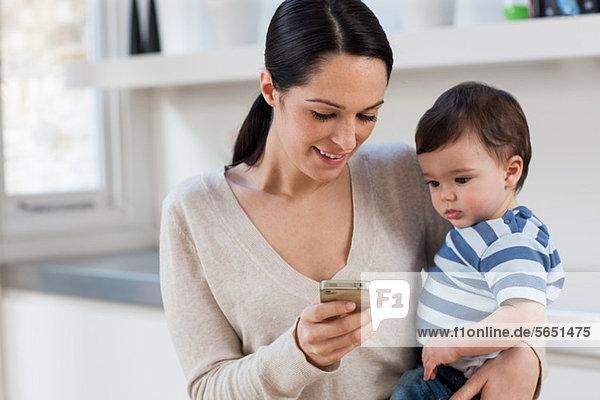 Mutter und Sohn schauen auf das Smartphone