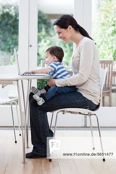 Young woman and baby son using laptop
