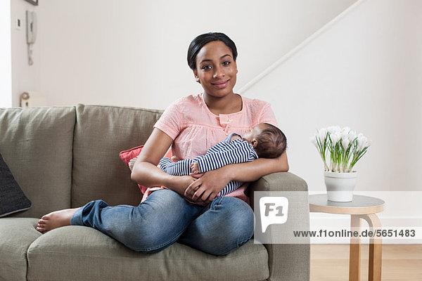 Junge Frau auf Sofa mit Baby-Sohn
